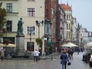 Nicolaus Copernicus surveys his birthplace, Toruń.